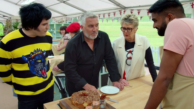 Judges and hosts gather around a contestant on the newest season of 'The Great British Baking Show.'