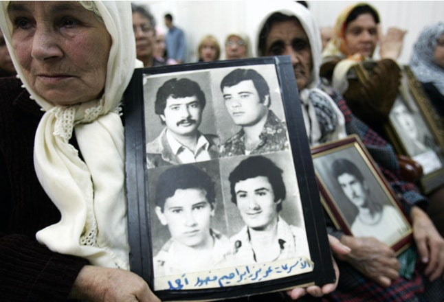 Relatives and friends of persons who disappeared during the war hold pictures of their loved ones