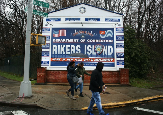 People walk by a sign at the entrance to Rikers Island on March 31, 2017 in New York.