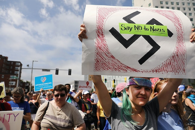 A protester holds up a sign condemning Nazis as thousands march through Boston on Saturday.