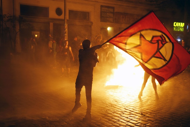 Riot police use a water cannon to put out burning bins as a protester holds a flag after the 'Welcome to Hell' rally against the G20 summit.