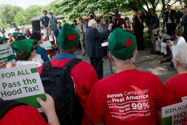 "Surrounded by students and members of National Nurses United in ""Robin Hood"" hats, Democratic Presidential candidate Sen. Bernie Sanders, I-Vt., center, speaks at a news conference on Capitol Hill in Washington, Tuesday, May 19, 2015, to discuss college tuition legislation."