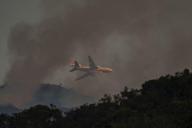 A firefighting jet flies low through the smoke of the Whittier Fire near Santa Barbara, California, July 9.