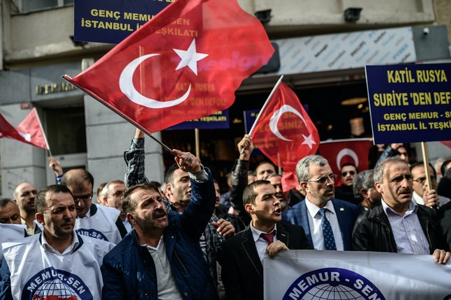 Protesters wave Turkish national flags outside of the Russian Istanbul Consulate building following the Turkish military downing a Russian SU-24.