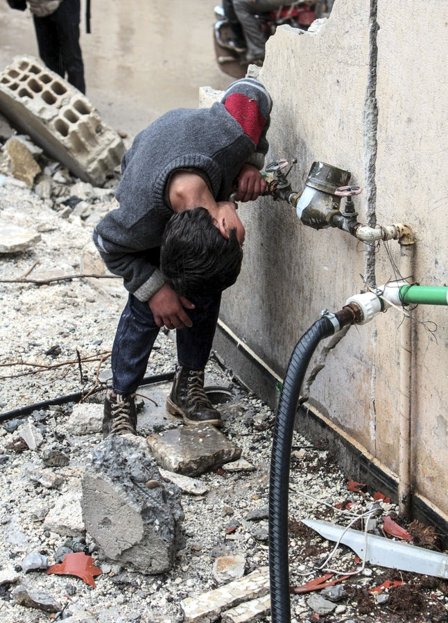 A boy drinks water from a tap on a damaged building in the center of the Syrian town of Kobani (Ayn al-Arab) on February 18, 2015 after it has been freed from Islamic State of Iraq and the Levant (ISIL) forces.