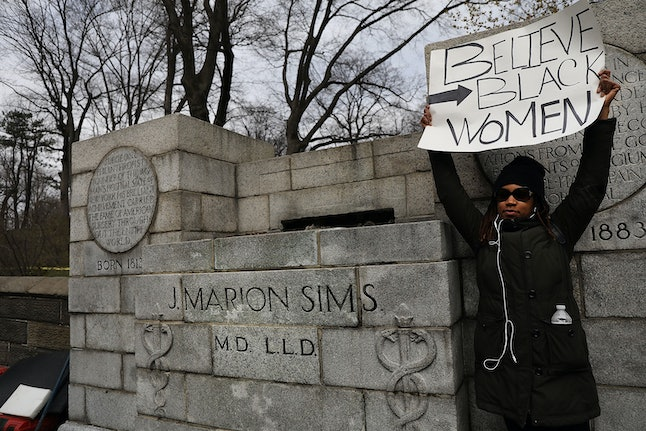 A woman stands beside the empty pedestal where a statue of J. Marion Sims, a surgeon celebrated by many as the father of modern gynecology, was taken down from its pedestal at Central Park and East 103rd Street on April 17 in New York City.