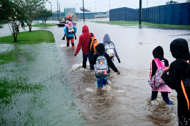 People walk to a Harris County Sheriff air boat while escaping a flooded neighborhood during the aftermath of Hurricane Harvey on Aug. 29 in Houston.