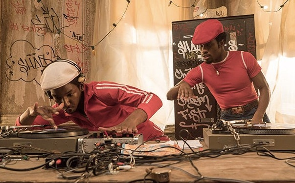 Grandmaster Flash teaches a young Shaolin Fantastic the intricacies of DJ'ing