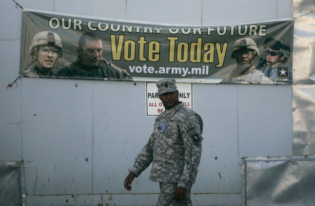 A U.S member of Combined Joint Task Force-101 walks past an election banner at a US military base in Bagram north of Kabul, Afghanistan, Oct. 15, 2008.  Soldiers, aid workers and military contractors in Afghanistan filled out absentee ballots that year.