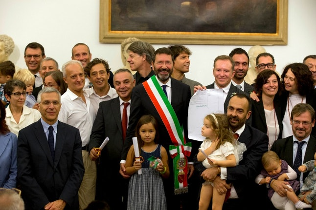 Rome's Mayor Ignazio Marino, center, poses for a group photo with gay couples after registering their gay marriages, in Rome, Saturday, Oct. 18, 2014. Marino has registered 16 gay marriages entered abroad in open defiance of Italy's Interior Ministry.