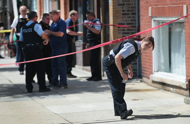 Police investigate a crime scene after two people were shot near Chicago's Westside on June 15.