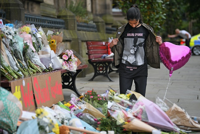 An Ariana Grande fan visits a floral tribute left for victims of the concert.