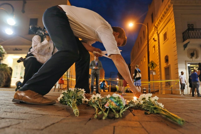 Charlottesville resident Elliot Harding lights a candle as he places flowers and a stuffed animal at a makeshift memorial for the victims after a car plowed into a crowd of people peacefully protesting a white nationalist rally earlier in the day in Charlottesville, Virginia, on Saturday.