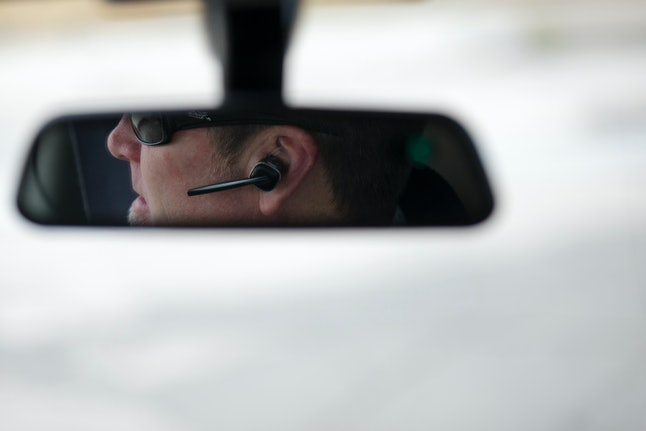 A driver is seen using a hands-free device while driving.