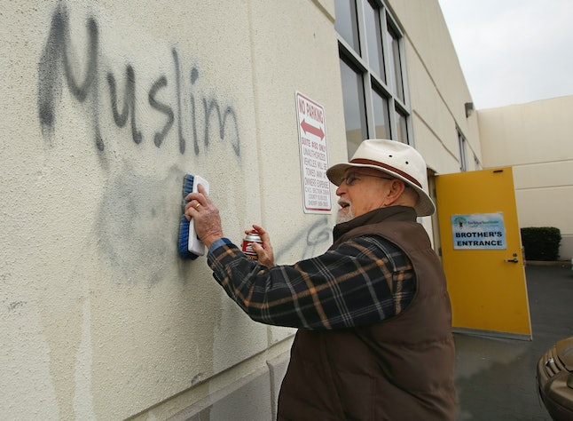 """A man cleans up racist graffiti painted on the side of a mosque in Roseville, California, on Feb. 1. The mosque was spray-painted with a dozen obscene and racist slurs, including """"Muslim out."""""""