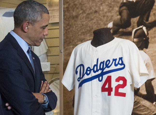 Obama looks at a jersey belonging to Jackie Robinson, the first black American to play in Major League Baseball, at the National Museum of African American History and Culture.