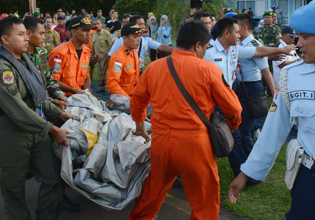 Indonesian Air Force personnel carry airplane parts recovered from the water near the site where AirAsia Flight 8501 disappeared, at the airbase in Pangkalan Bun, Central Borneo, Indonesia, Tuesday, Dec. 30, 2014.