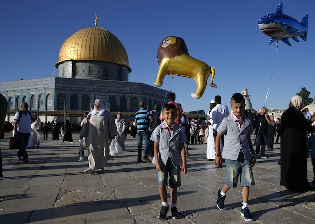 Palestinian boys hold balloons as people gather for the morning Eid al-Fitr prayer near the Dome of Rock at the Al-Aqsa Mosque in the Old City of Jerusalem.