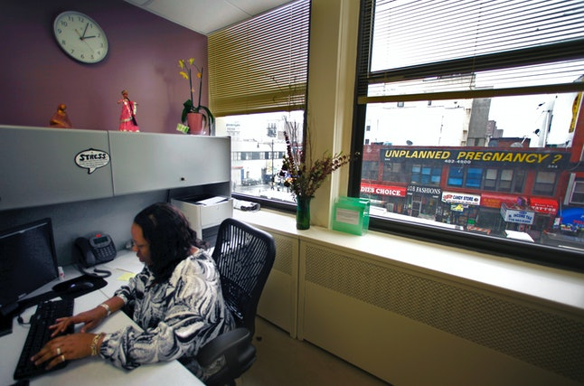 Felicia Morris-Bolar, center director of Planned Parenthood in the Bronx, N.Y., works in her office with a view from her window of the EMC Pregnancy Center signage.