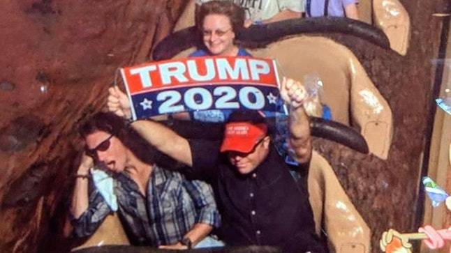 Dion Cini holds a Trump 2020 banner on Splash Mountain at Disney World in Orlando, Florida.