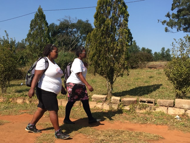 Luthuli (left) and Luhlongwane walk to a house to conduct an HIV test.