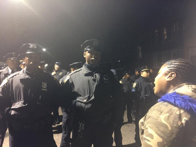 A protester confronts police on Thursday night near a vigil for Saheed Vassell, who was fatally shot by NYPD officers.