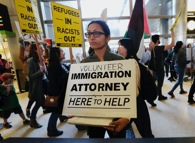 A woman offers legal services at the customs arrival area as demonstrators opposed to President Donald Trump's travel ban march behind at Los Angeles International Airport.