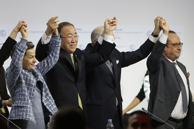 Global leaders including Ban Ki Moon and Francois Hollande celebrate the finalization of the Paris global warming pact in December 2015.