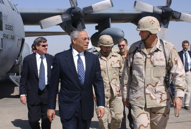 Former U.S. Secretary of State Colin Powell talks with military personnel in Kirkuk, Iraq, in September 2003.