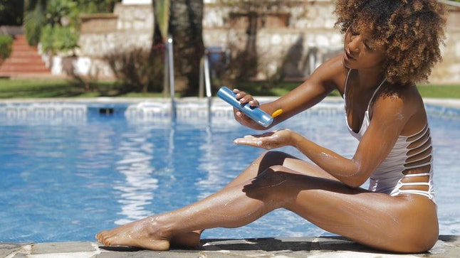 A woman applying sunscreen.