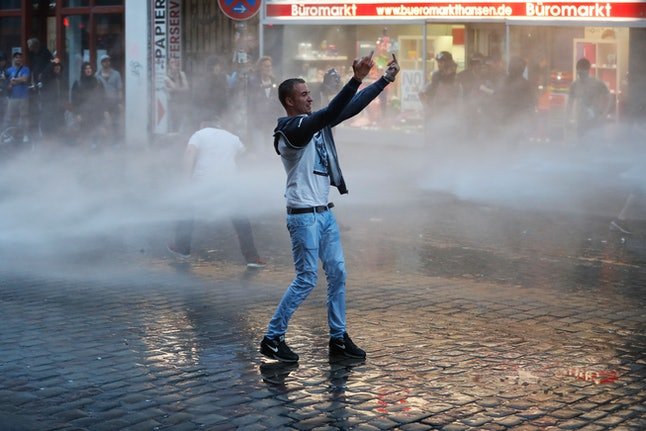 A protester gestures at riot police at the G20 summit.