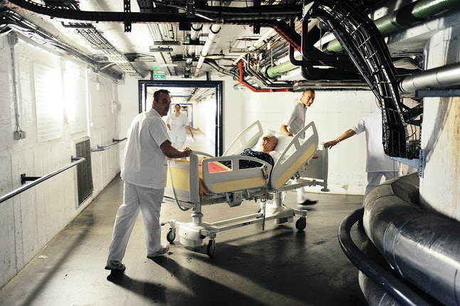 Male healthcare assistants shift a patient in a hospital.