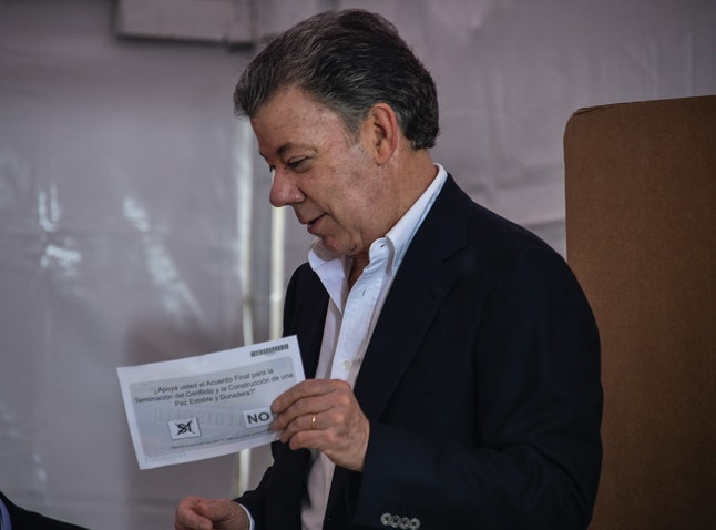 Colombian President Santos holds up his referendum ballot, marked in favor of the peace deal.