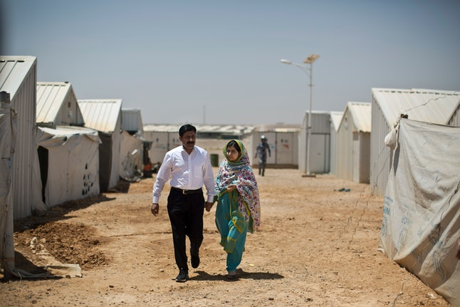 Malala Yousafzai and her father walk through an Azraq refugee camp, July 13, 2015.