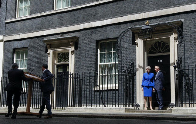 British Prime Minister Theresa May and her husband Philip stand on the doorstep of 10 Downing street, London on June 9, 2017. May's gamble in calling an early election backfired spectacularly, as her Conservative Party lost its majority in Parliament.