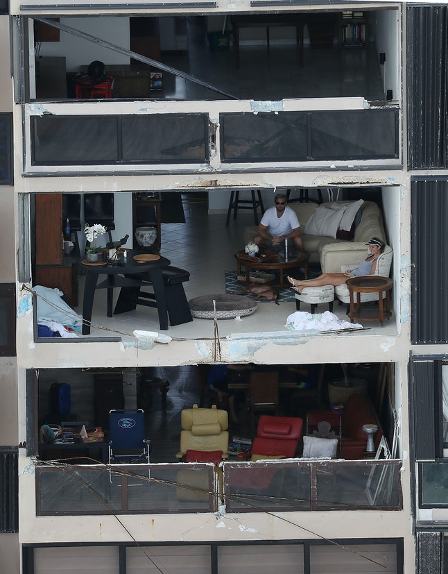People sit in their apartment in San Juan, Puerto Rico, after the window was blown out by the winds of Hurricane Maria.