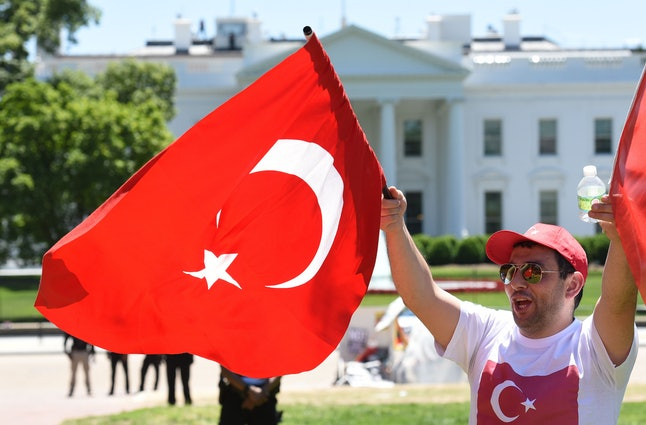 Pro-Erdogan supporters wave Turkish flags at anti government protesters in front of the White House in Washington, D.C.