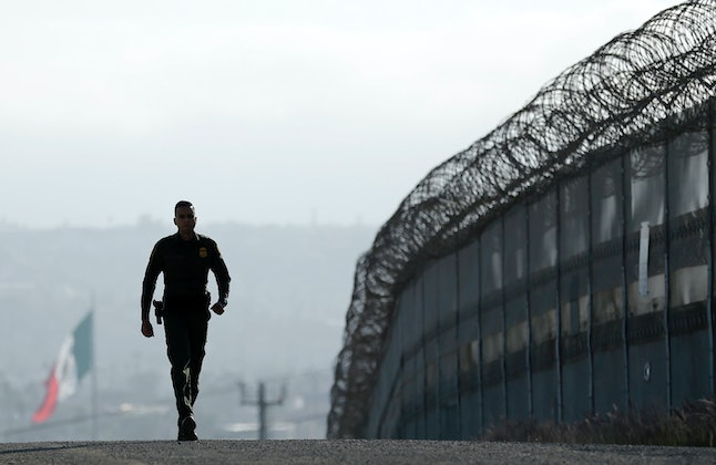 A border patrol agent walks along the border separating San Diego, California and Tijuana, Mexico in June 2016.