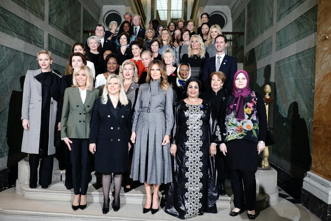 French President Emmanuel Macron's wife, Brigitte Macron, second left, poses with U.S first lady Melania Trump, center, and other leaders' companions at the Palace of Versailles on Sunday.