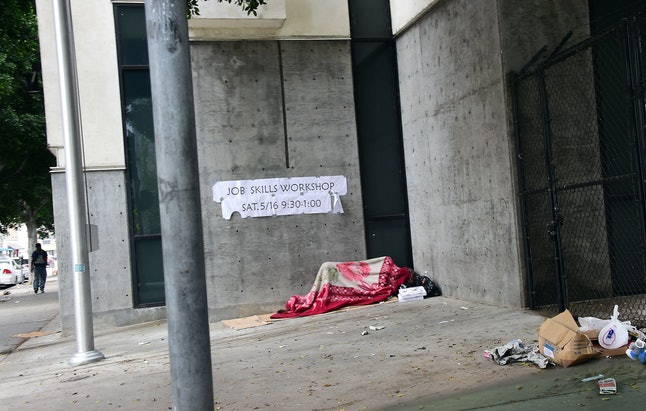 A homeless person sleeps covered with a blanket on a sidewalk near Skid Row in Los Angeles, California.