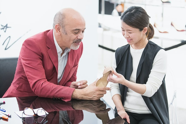 Fashion designer Christian Louboutin with a customer at a Nordstrom in Seattle