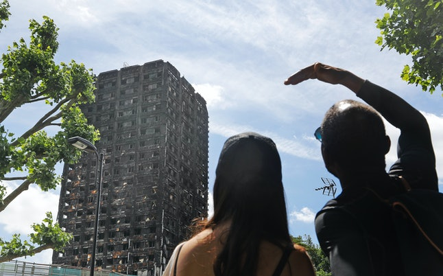People look at the burnt Grenfell Tower apartment building in London on June 23.