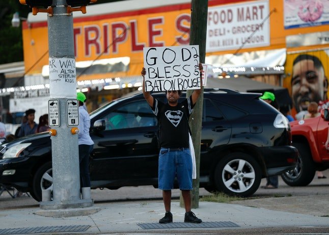 Protester holds up a sign outside the Triple S Food Mart, where Alton Sterling was killed following DOJ decision not to charge officers.