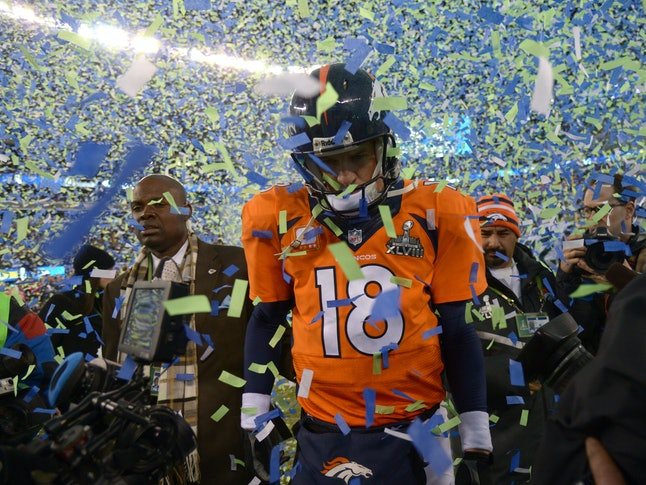 "Sad Peyton Manning walks through cloud of confetti following the Seahawks' win, sports face that doesn't say ""pay day."""
