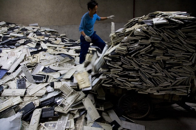 Worker sorting through computer keyboards in Guiyu, China, where 5,500 family workshops handle e-waste.