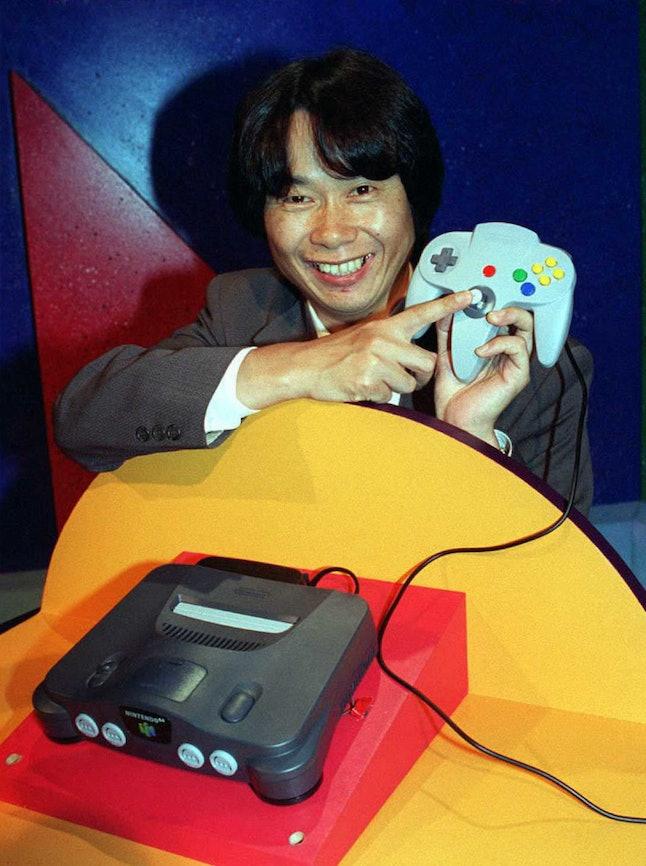Video game designer Shigeru Miyamoto points to the Nintendo 64 controller.