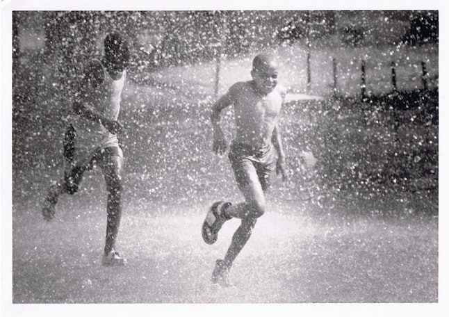 """Chicago boys open a hydrant in June 1987 at 44th & Champlain Ave. This photo from the Chicago Defender Archives is featured in the Obsidian Collection Archives story """"Hot Fun in the Summertime."""""""