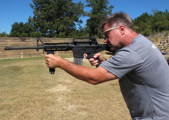 """Shooting instructor Frankie McRae aims an AR-15 rifle fitted with a """"bump stock"""" at his 37 PSR Gun Club in Bunnlevel, North Carolina, on Oct. 4, 2017."""