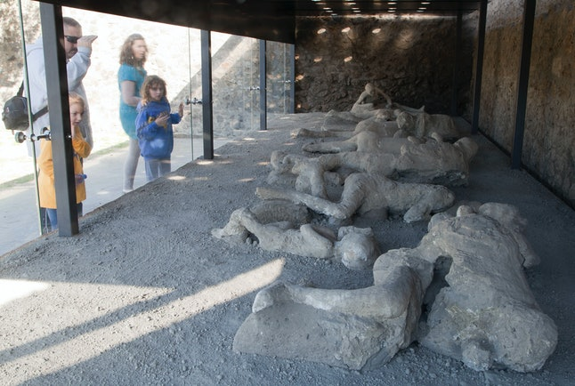 A family observing preserved bodies of Pompeii victims at 'The Garden of the Fugitives' in Italy.