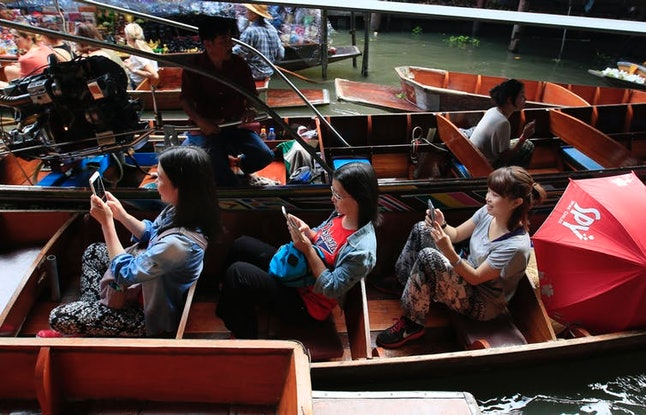 Tourists looking at their mobile phones instead of the passing sights at the famous Damnoen Saduak Floating Market, Bangkok, in February 2015. EPA/BARBARA WALTON